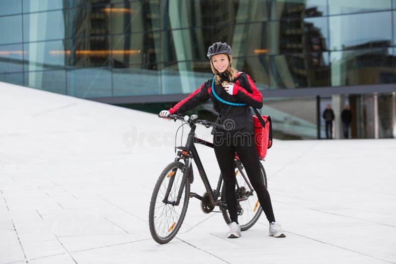 有传讯者交付袋子的女性骑自行车者使用 免版税库存照片