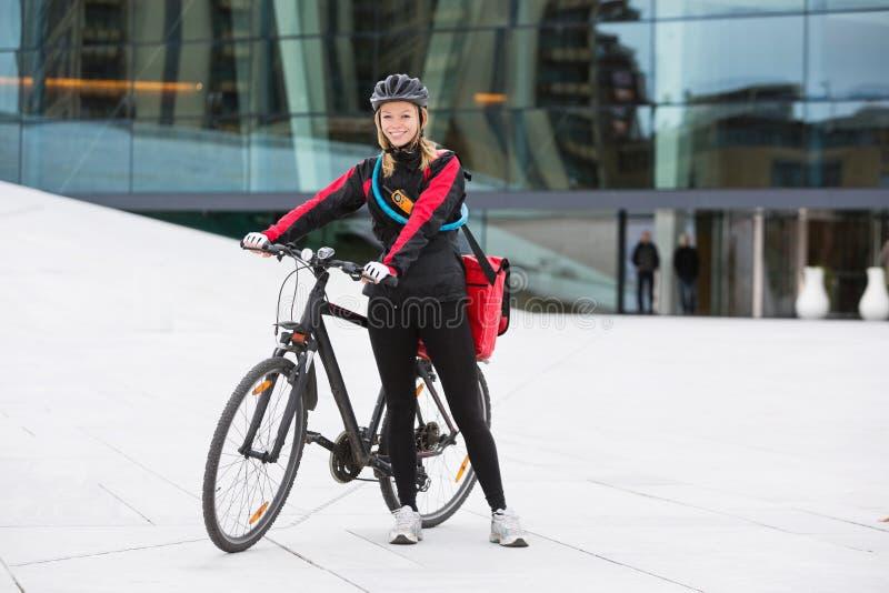 有传讯者交付袋子的女性骑自行车者 免版税库存图片