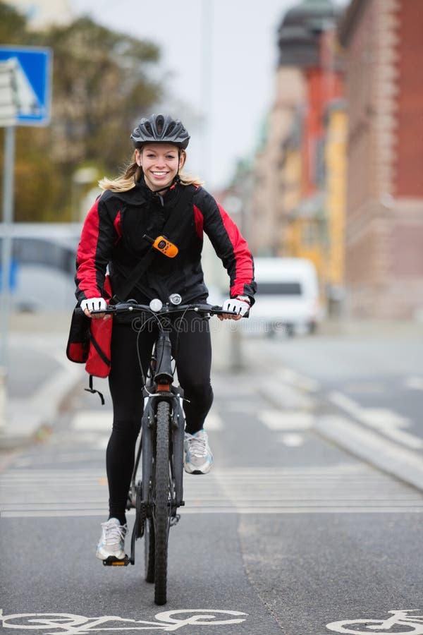 有传讯者交付袋子的女性骑自行车者 库存照片