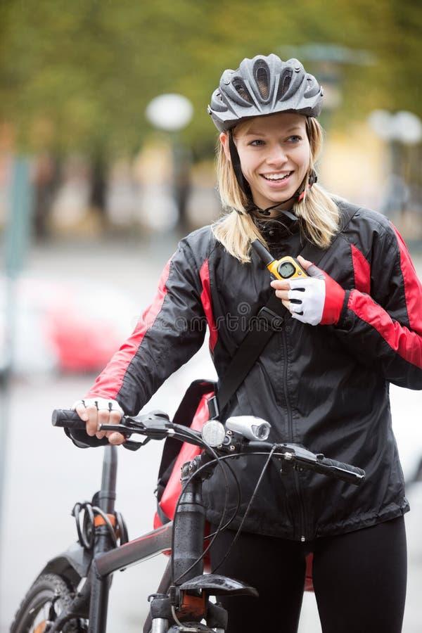 有传讯者袋子的女性骑自行车者使用 库存图片