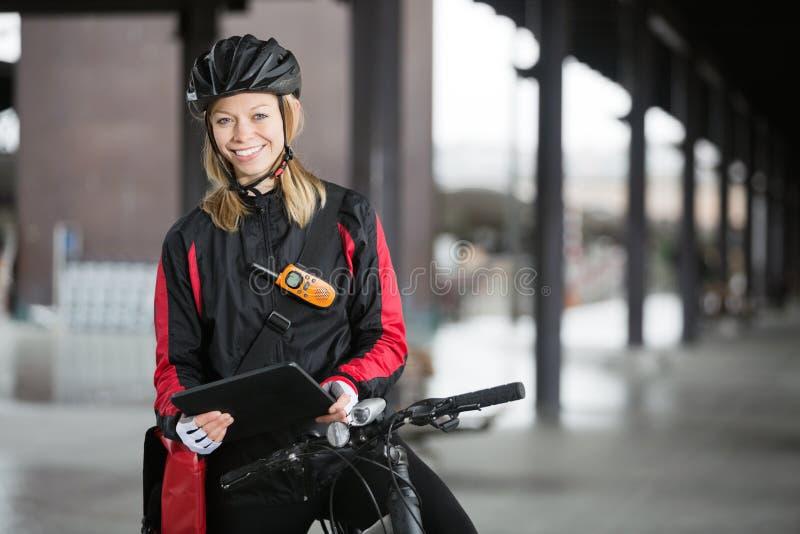 有传讯者袋子的女性骑自行车者 免版税库存图片