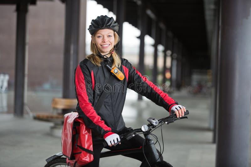 有传讯者袋子的女性骑自行车者 库存照片