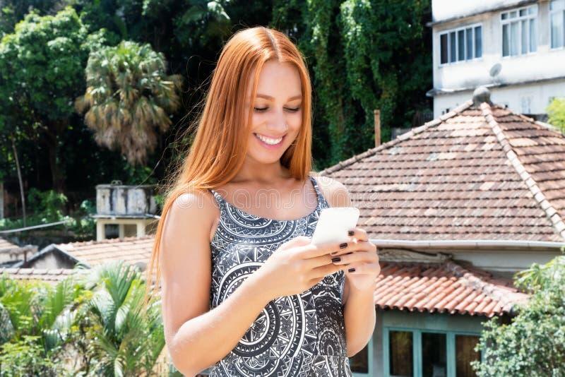 有传送与手机的红色头发的女性游人信息 免版税库存照片