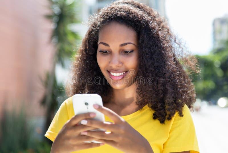 有传送与电话的卷发的美丽的拉丁妇女信息 库存照片