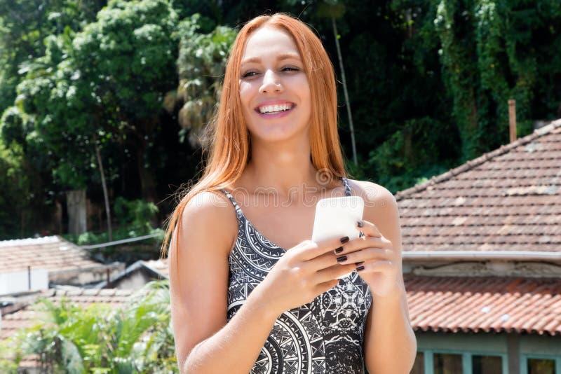 有传送与m的红色头发的笑的世界观光旅行家妇女信息 库存图片