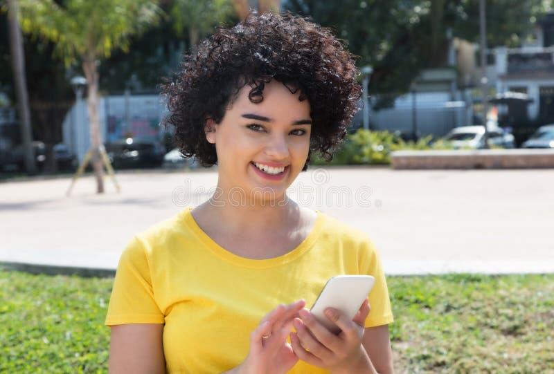 有传送与MOBIL的卷发的年轻白种人妇女信息 库存照片