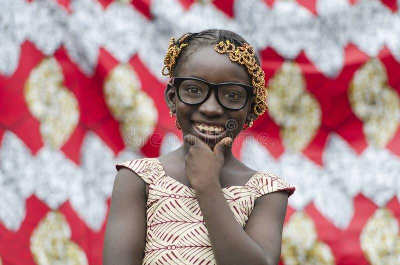 有传统辅助部件的美丽的年轻非洲女孩在头发微笑对照相机的 图库摄影