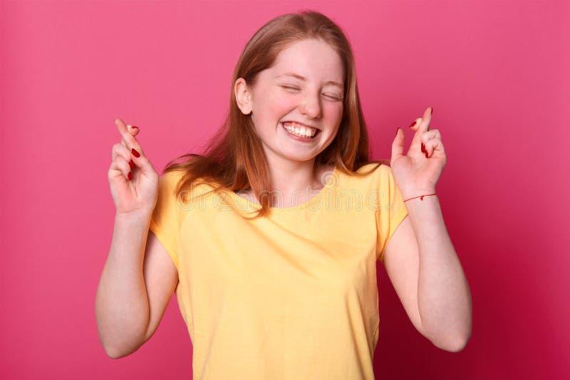 有但愿的快乐的年轻美女,做愿望,广泛地微笑,穿偶然黄色T恤杉,在桃红色墙壁的模型 免版税库存图片