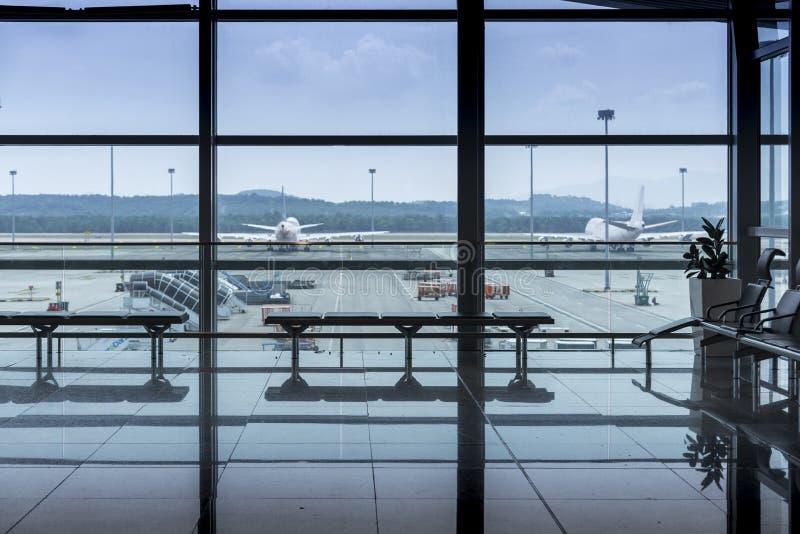 有位子和玻璃框架和反射窗口的国际机场内部走廊在机场终端离开大厅里 免版税库存图片