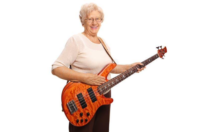有低音吉他的微笑的年长妇女 免版税库存照片