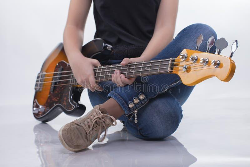 有低音吉他的坐的女孩 库存图片