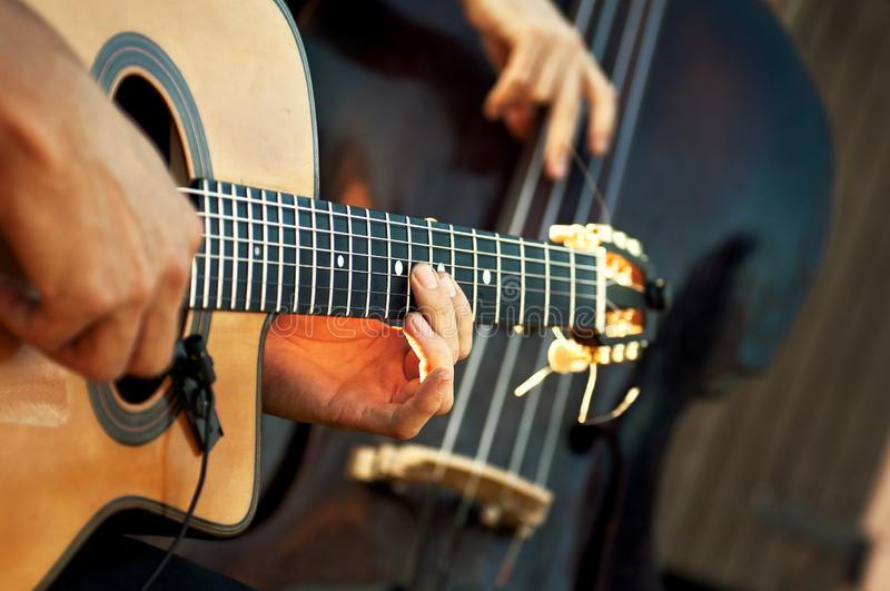 有低音提琴的声学吉他在展示期间的音响小组 免版税库存照片
