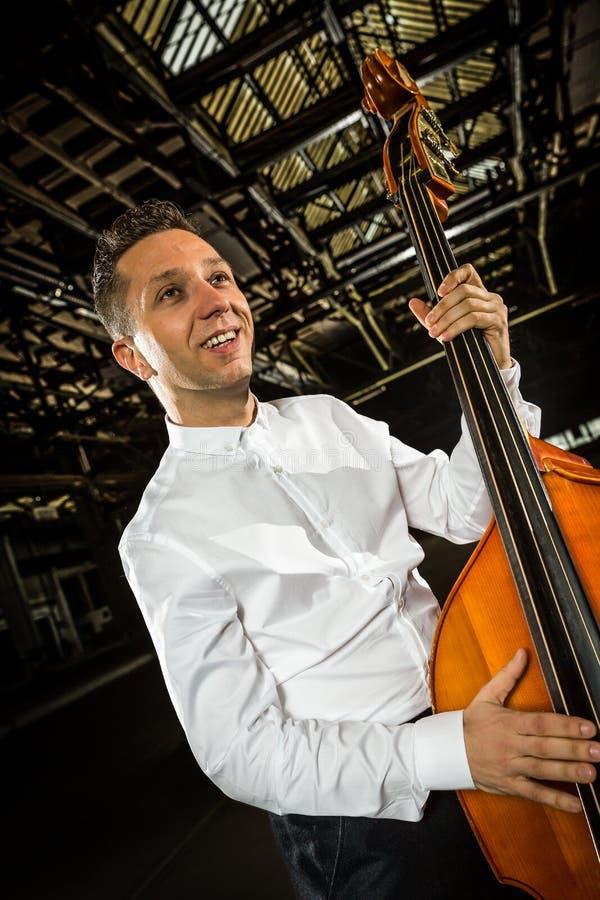 有低音提琴球员的人的白色衬衣 库存图片