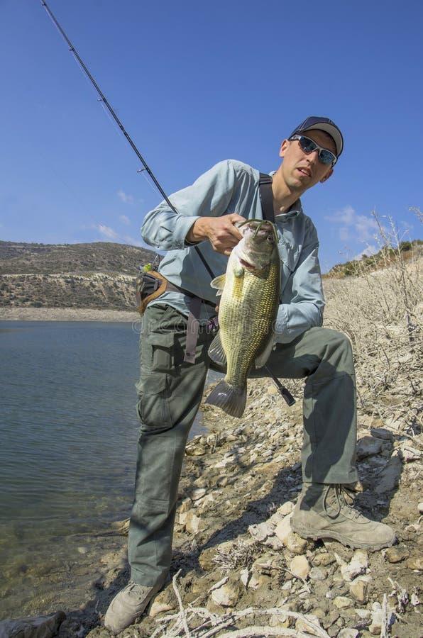 ?? 有低音鱼的渔夫在手中 免版税库存图片