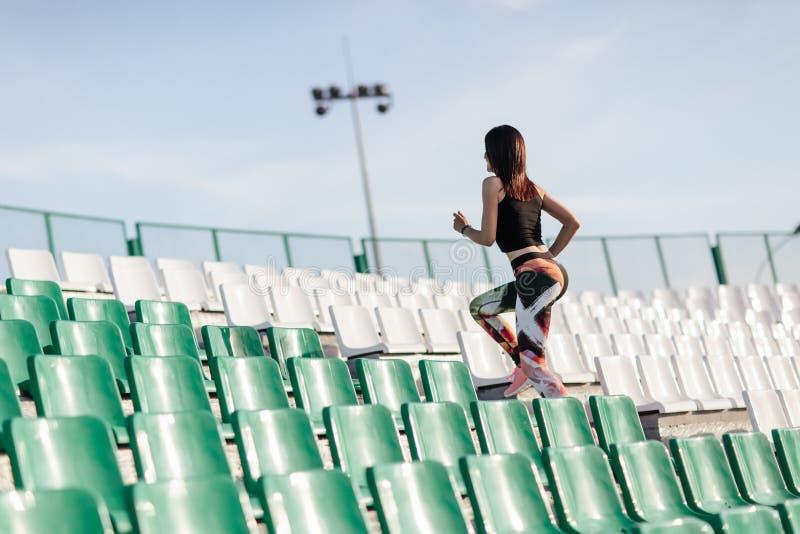 有体育形象在绑腿和黑顶面赛跑的年轻健身妇女在体育场的石台阶有太阳斑点的 图库摄影