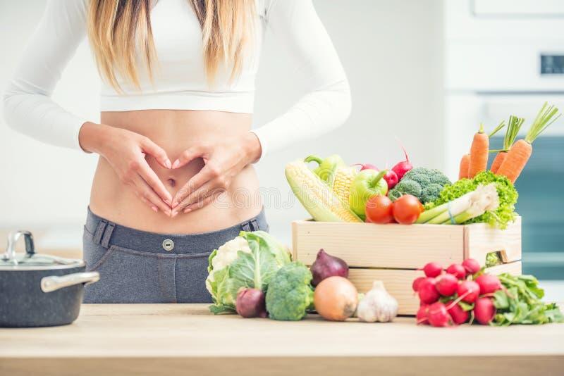 有体育形象的妇女在她的腹部在有木箱的家庭厨房充分显示心形有机蔬菜 库存照片