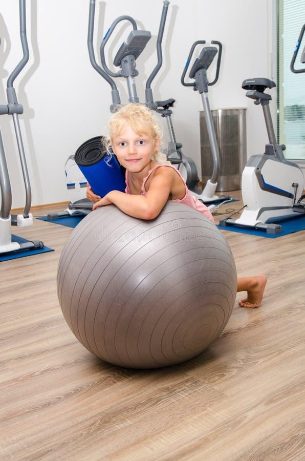 有体育球的小女孩在健身房 免版税图库摄影