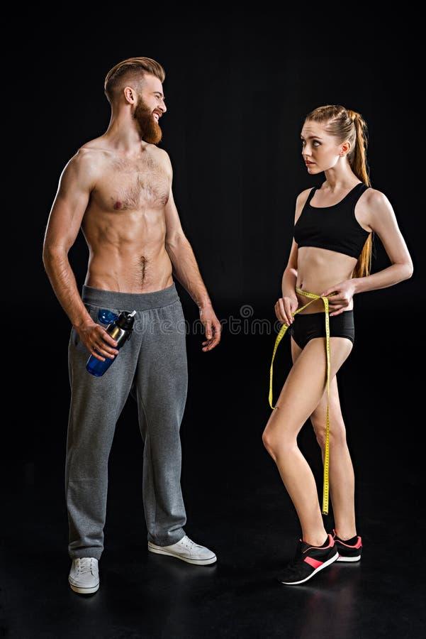 有体育瓶和女运动员的有胡子的运动员有测量的磁带的 免版税库存图片