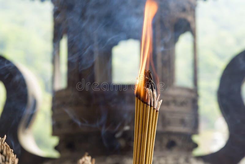 有佛教寺庙的燃烧的香火棍子在背景中 免版税库存图片