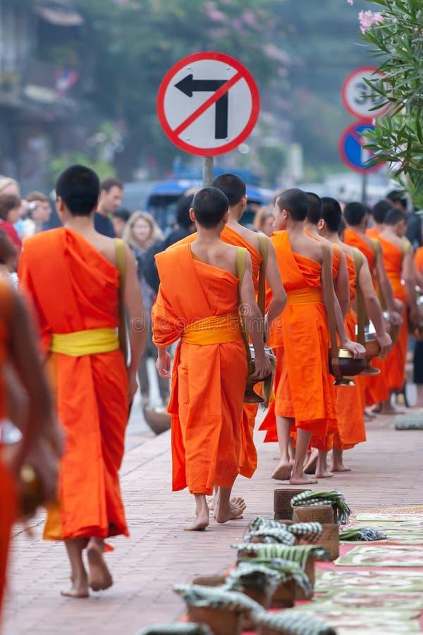 有佛教救济仪式的游人照相老挝和尚在路在早晨,传统给 库存图片
