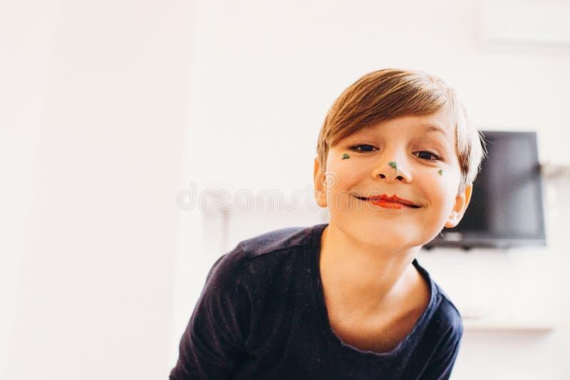 有作为小丑被绘的面孔的逗人喜爱的男孩,微笑 免版税库存图片