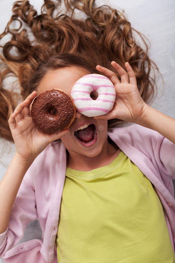 有作为玻璃使用的两个油炸圈饼的愉快的少年女孩-呼喊 免版税库存图片