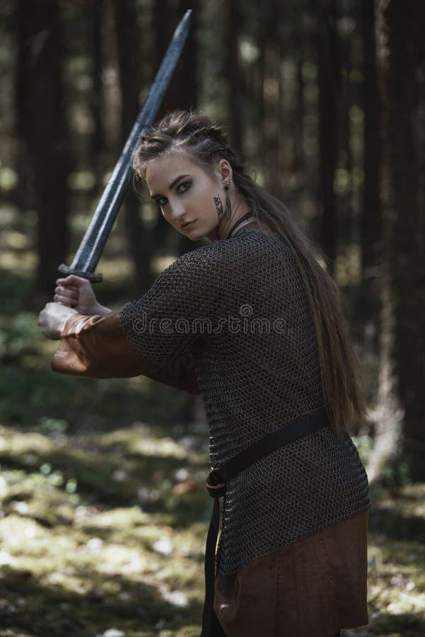 有佩带传统战士的剑的北欧海盗妇女在一个深神奇森林穿衣 免版税库存图片