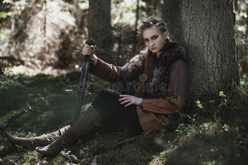 有佩带传统战士的剑的北欧海盗妇女在一个深神奇森林穿衣 免版税库存照片