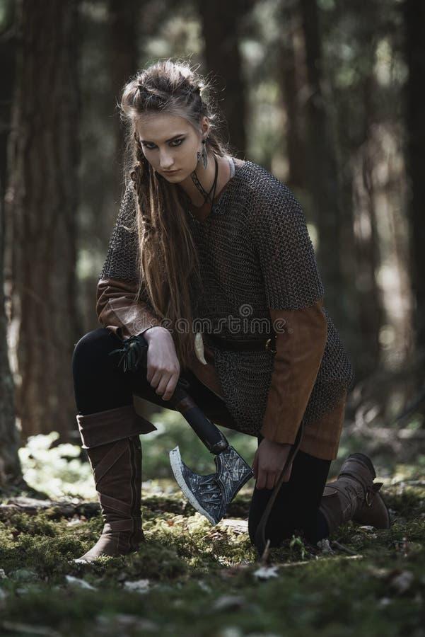 有佩带传统战士的锤子的北欧海盗妇女在一个深神奇森林穿衣 库存照片