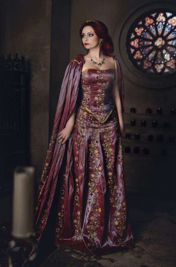 有佩带典雅的皇家服装的红色头发的妇女 免版税库存照片