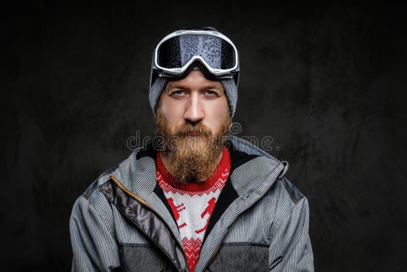 有佩带极端雪板运动的一个红色胡子的确信的人一种充分的设备,看与严肃的一台照相机 免版税库存图片