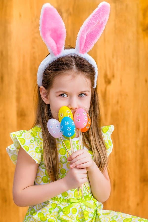 有佩带桃红色和白色兔子或兔宝宝耳朵和拿着的长的金发的微笑的小女孩束被绘的五颜六色的鸡蛋 库存图片