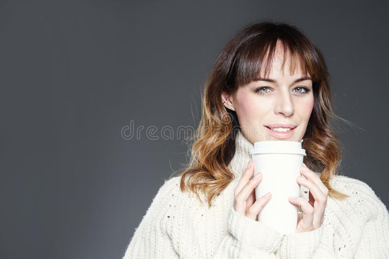 有佩带红色帽子和毛线衣举行的长发的美女显示纸一次性咖啡杯 设计模板的空间 免版税库存图片