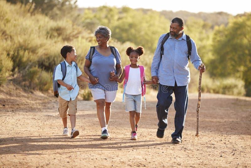 有佩带背包的孙的祖父母一起远足在乡下 免版税库存照片