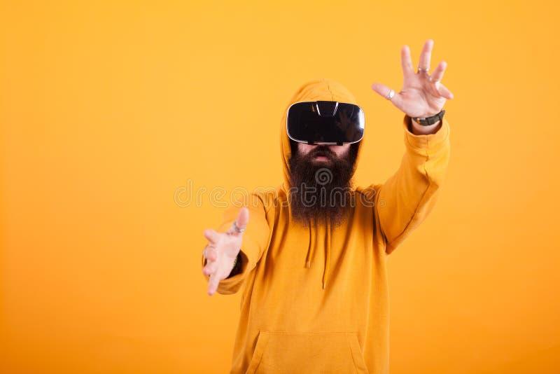 有佩带虚拟现实耳机的长的胡子的可爱的年轻人做在黄色背景的手势 库存照片