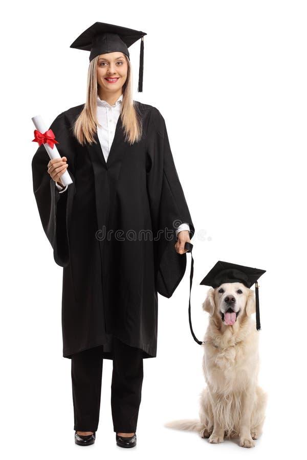 有佩带gradu的文凭和狗的女性研究生 免版税库存照片