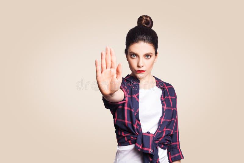 有使与她的棕榈的坏态度的年轻懊恼妇女中止姿态向外,反对,表达否认或制约 库存照片