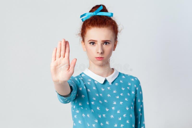 有使与她的棕榈的坏态度的年轻懊恼红头发人女孩中止姿态向外,反对,表达否认 免版税库存图片