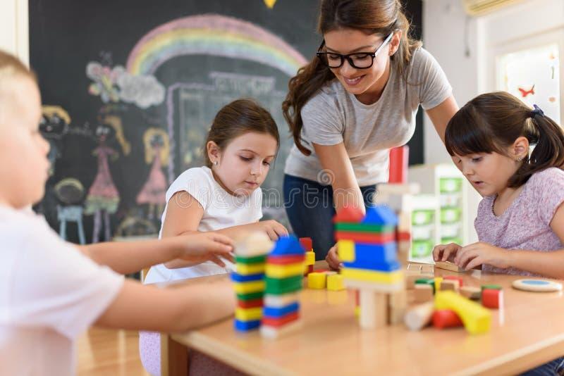 有使用与五颜六色的木教诲玩具的孩子的学龄前老师在幼儿园 免版税库存照片
