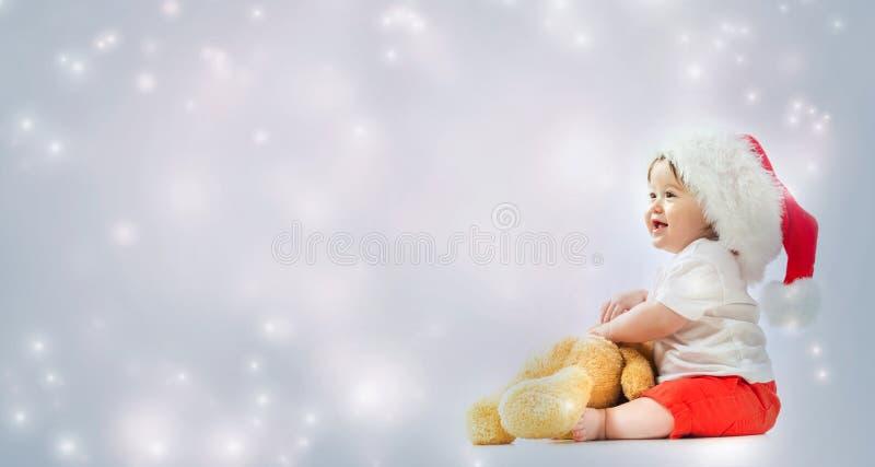 有使用与他的玩具熊的圣诞老人帽子的小孩男孩 免版税库存图片