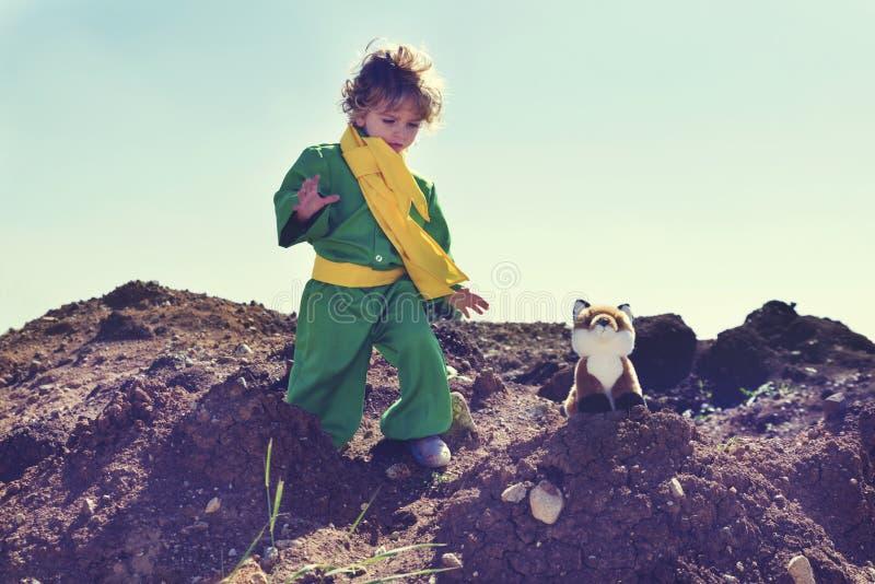 有使用与在地球上穿绿色衣裳和黄色围巾的堆的豪华的狐狸玩具的卷曲金发的逗人喜爱的男孩 免版税库存图片