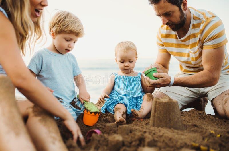 有使用与在海滩的沙子的小孩孩子的年轻家庭在度假夏天休假 免版税库存图片