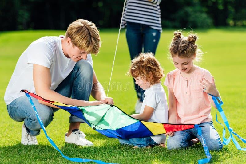 有使用与在绿草的风筝的两个孩子的愉快的父亲 免版税库存照片