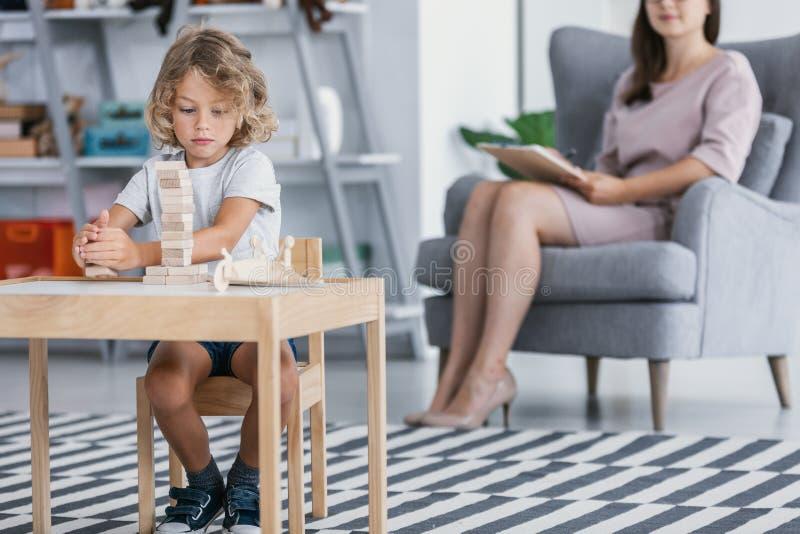 有使用与木块的亚斯伯格综合症状的一个孩子在与一位治疗师的一次治疗会谈期间在家庭供应中心 库存照片