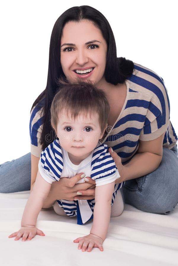 有使用在地板上的母亲的爬行的女婴,被隔绝 免版税图库摄影