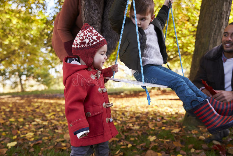 有使用在树摇摆的孩子的父母在秋天庭院里 免版税库存图片