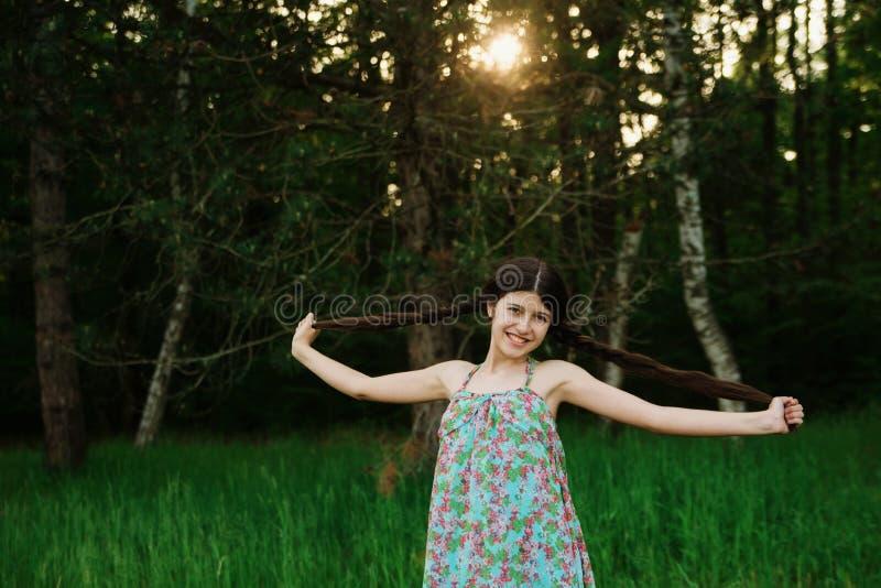 有使用在森林里的长的头发的好女孩 免版税库存图片