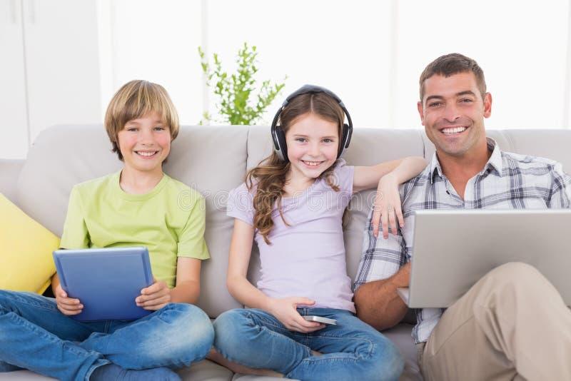 有使用在沙发的孩子的愉快的人技术 免版税图库摄影