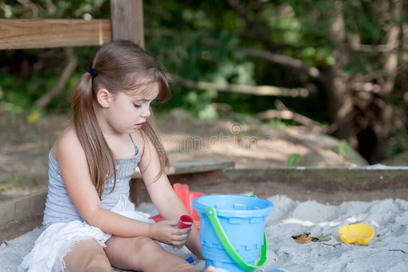 有使用在沙盒的两条猪尾巴的可爱的小女孩在被遮蔽的后院 免版税库存照片