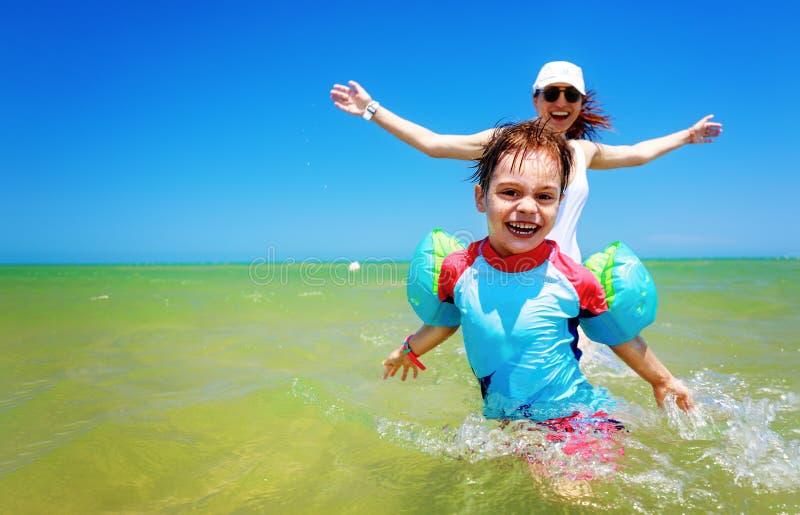 有使用在海滩的水中的儿子的幸福家庭母亲在夏天 使用在海滩的母亲和儿子 家庭度假 免版税库存照片